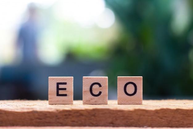 Ecowoord van houten kubus op groene aard als achtergrond