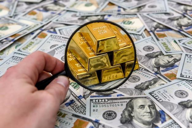 Edelmetaal, goud of baar op het biljet van de amerikaanse dollar met vergrootglas
