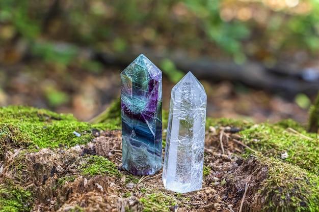 Edelstenen fluoriet, kwartskristal. magische rots voor mystiek ritueel, hekserij wicca en spirituele oefening op boomstronk in bos