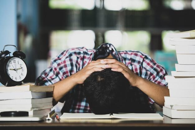 Educatief concept: vermoeide student in een bibliotheek