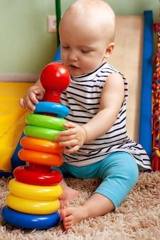Educatief logisch speelgoed voor kinderen. een kind verzamelt een gekleurde piramide. montessori-spellen voor de ontwikkeling van het kind. vroege ontwikkeling