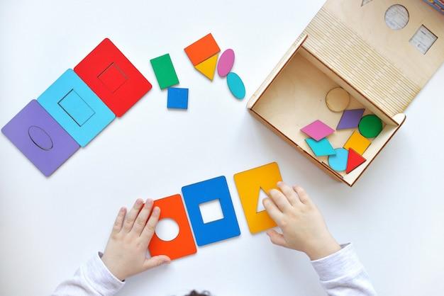 Educatief logisch speelgoed voor kinderen. kleuren en vormen leren. houten speelgoed voor kinderen. het kind haalt een sorteerder op.