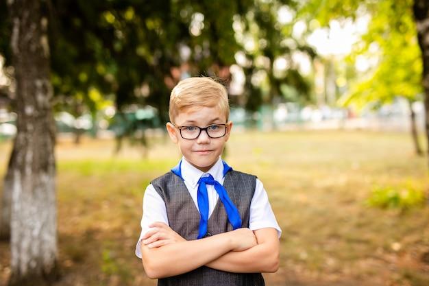 Educatief thema: portret van een schooljongen met grote zwarte bril en blauwe stropdas. achtertuin, begin van de lessen