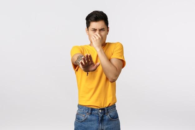 Eeew stinkt. weerzinwekkende aziatische man in geel t-shirt, bedek neus van afkeer, ruik iets vreselijks, beschuldig of beschuldig persoon stinkt, staande witte muur ontstemd