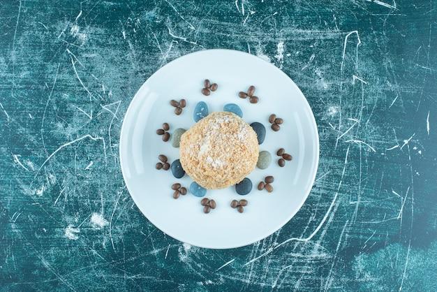 Eekhoorncake op een schotel met snoeprotsen en koffiebonen op blauw.