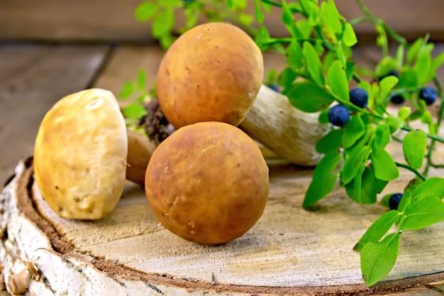 Eekhoorntjesbrood, twijgen met groene bladeren en bosbessen op een berkstaaf op de achtergrond van houten planken
