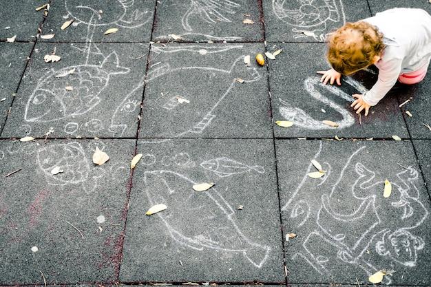Een 1-jarige baby speelt zittend op de vloer van een park met wat krijt om op de zwarte grond te tekenen.