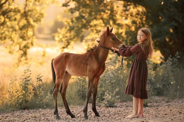 Een 12-jarig meisje loopt op blote voeten in een veld met een klein paard
