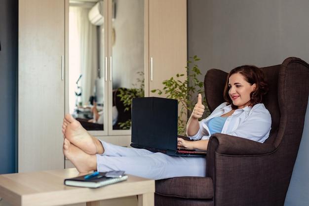 Een 30-jarige jonge vrouw in een wit overhemd zit thuis in een comfortabele fauteuil en communiceert met familieleden via een laptop en videobellen.