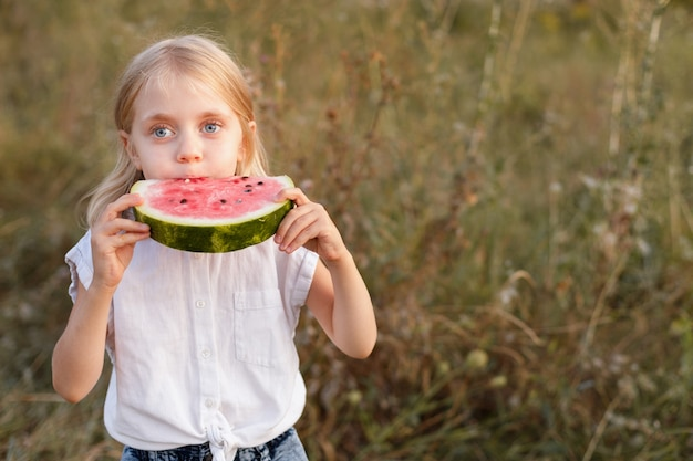Een 5-jarig meisje eet in augustus watermeloen tijdens een wandeling. toetje