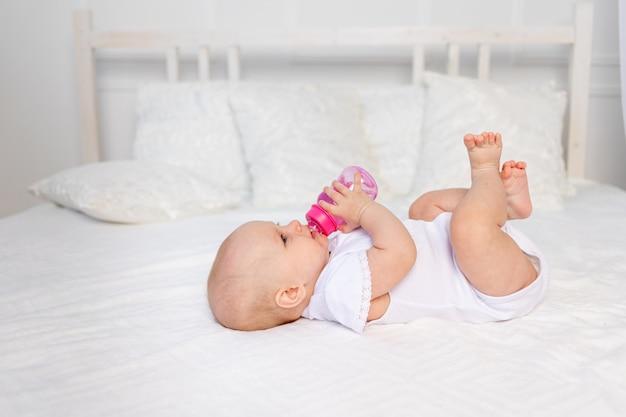Een 6 maanden oude baby ligt op een wit bed en drinkt melk uit een fles, babyvoedingconcept, tekstruimte