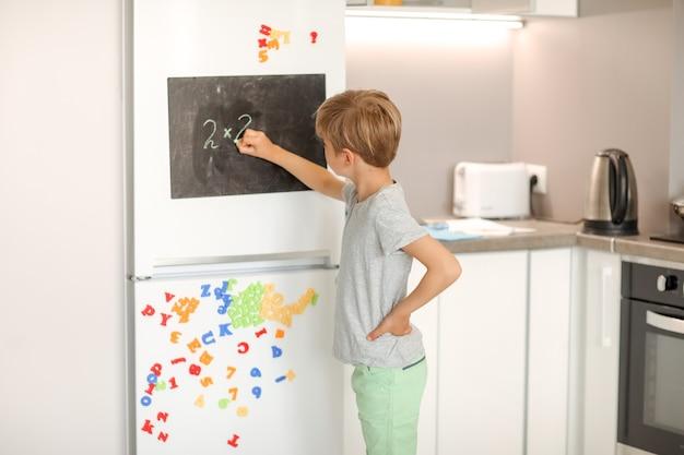Een 8-jarige schooljongen schrijft wit krijt op een magnetisch zwart bord dat aan een koelkast is bevestigd.