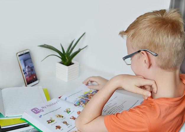 Een 9-jarige jongen houdt zich bezig met afstandsonderwijs, online les thuis, sociale afstand tijdens quarantaine. zelfisolatie. concept online onderwijs, thuisonderwijs