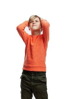 Een 9-jarige jongen houdt zijn hoofd vast met zijn handen en kijkt op.