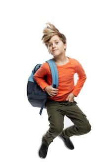 Een 9-jarige jongen met een modieus kapsel in een oranje trui met een rugzak springt