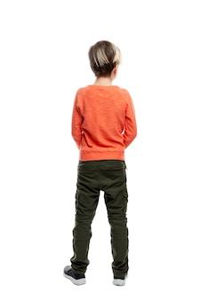 Een 9-jarige jongen staat in een spijkerbroek en een oranje trui
