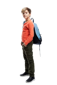 Een 9-jarige schooljongen in spijkerbroek en oranje trui staat met een rugzak