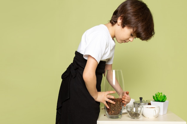 Een aanbiddelijk snoepje die van de vooraanzicht de leuke jongen koffiedrank op de lijst aangaande de steen gekleurde ruimte voorbereiden