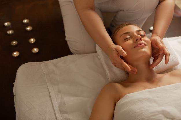 Een aangename massage ontvangen. knappe jonge vrouw met vastgebonden haar die uiterst tevreden is met cosmetische ingreep