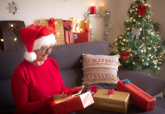 Een aangename verrassing. de oude dame met kerstmuts krijgt een nieuwe tablet als kerstcadeau. een senior mensen zittend op de bank. kerstboom en cadeautjes op de achtergrond
