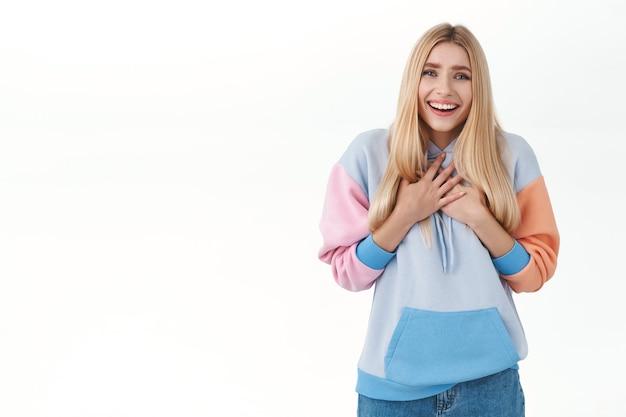Een aangeraakt blij, glimlachend meisje voelt zich gevleid en verheugd om een schattig, schattig cadeau te ontvangen, hand in hand op de borst