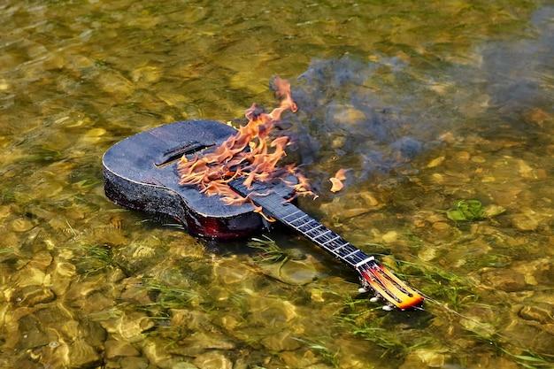 Een aangestoken gitaar drijft op de rivieroever, vuur brandt op het oppervlak.