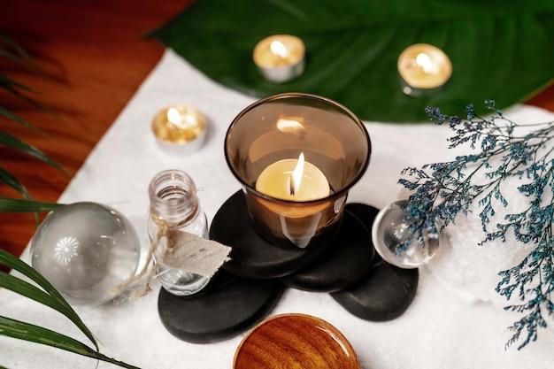 Een aangestoken kaars die op stenen staat voor een therapiesteen met aromatische olie op een badstofhanddoek met daarop transparante bollen, een gedraaide witte badstofhanddoek en een takje lavendel