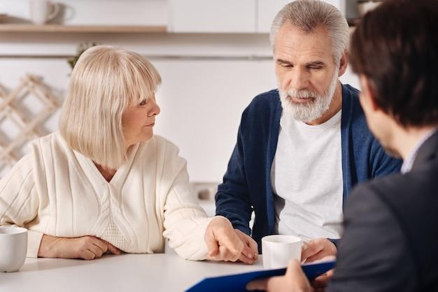 Een aankoop doen. beslissend betrokken senior koppel dat thuis zit en een gesprek voert met adviseur terwijl ze interesse tonen