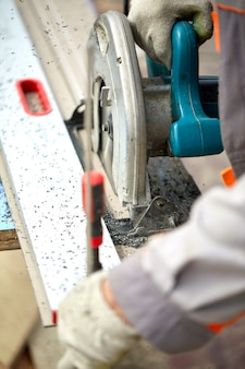 Een aannemer in de bouw die een worm aangedreven handcirkelzaag gebruikt om planken en plastic te zagen. bouw, eigen werkplaats, inhuren van een werkcontract om hout te zagen.