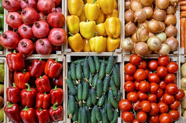 Een aanrecht met verschillende groenten in laden is mooi en gelijkmatig van bovenaf ingedeeld. wortelen aardappels komkommers, paprika, uien, tomaten.