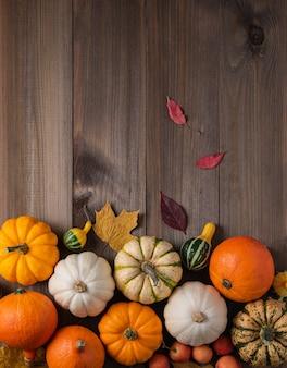 Een aantal decoratieve kleurrijke pompoenen en blad op houten bruin.