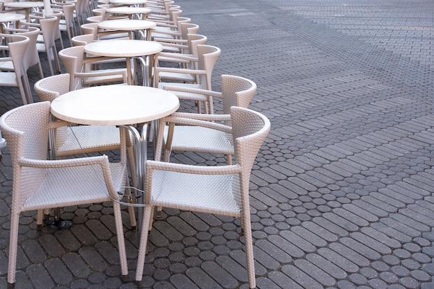 Een aantal lege tafels met stoelen zijn verbonden door een kabel van diefstal in een café aan de straat.