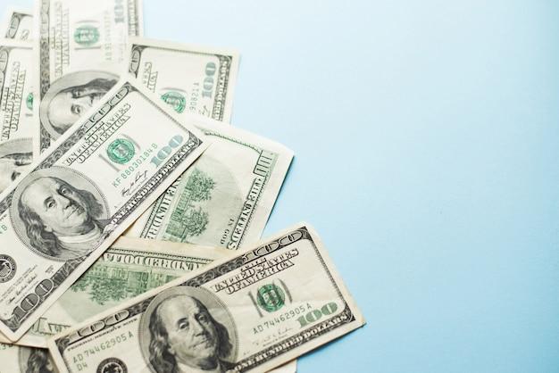 Een aantal van honderd us dollar biljetten op lichtblauw