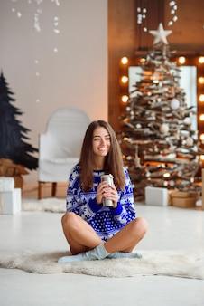 Een aantrekkelijk glimlachend meisje in een blauwe nieuwjaarssweater zit op een warm wit tapijt
