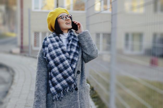 Een aantrekkelijk jong meisje draagt een zonnebril in een jas die op straat loopt en aan de telefoon spreekt en glimlacht