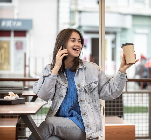 Een aantrekkelijk meisje in een casual stijl drinkt koffie op het zomerterras en praat aan de telefoon.