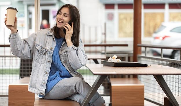 Een aantrekkelijk meisje in een casual stijl drinkt koffie op het zomerterras en praat aan de telefoon