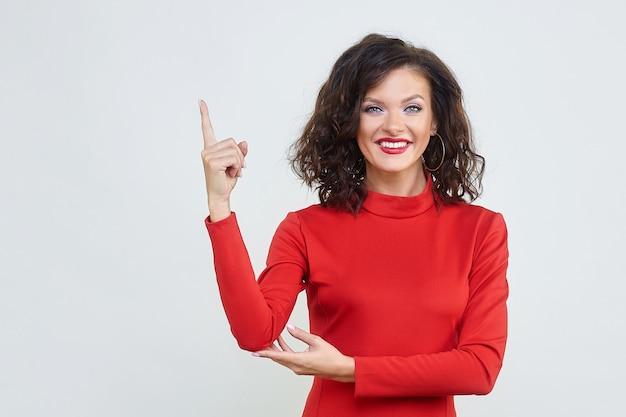 Een aantrekkelijk meisje in een rode jurk houdt haar wijsvinger omhoog
