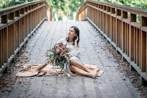 Een aantrekkelijk meisje in een witte jurk zit op de brug met een boeket exotische bloemen.