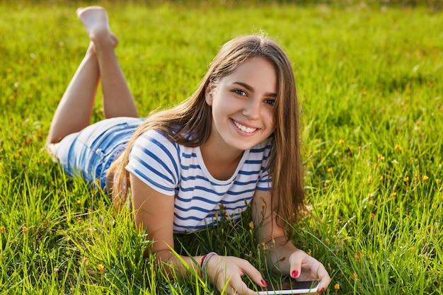 Een aantrekkelijk meisje met aangename glimlach en donker lang haar dat en op het gras ligt ontspant dat haar smartphone in haar handen houdt. een vrij gelukkig meisje dat de zomer en zonnig weer op de weide enyoing