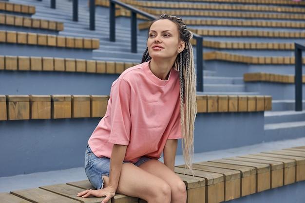 Een aantrekkelijk meisje met dreadlocks zit op de trap en kijkt weg stadsgezicht hoge kwaliteit foto