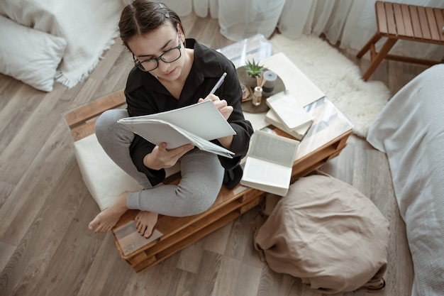 Een aantrekkelijk meisje met een bril schrijft iets in een notitieboekje, studeert of werkt thuis op afstand.