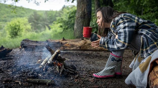 Een aantrekkelijk meisje met een kopje in haar hand warmt op bij een vuur in het bos.