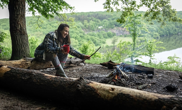 Een aantrekkelijk meisje met een kopje in haar hand zit op een boomstam en verwarmt zichzelf bij een vuur in het bos.