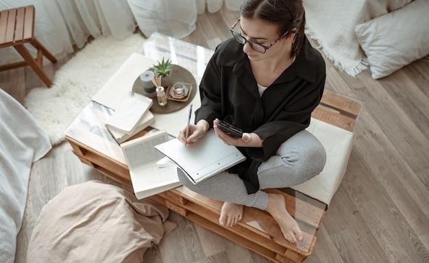 Een aantrekkelijk meisje schrijft thuis iets in een notitieboekje met een telefoon in haar handen.