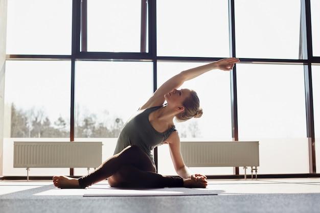 Een aantrekkelijk meisje zit in kleermakerszit, bukken, het uitvoeren van een yoga asana. het meisje doet yoga in een moderne studio met panoramische ramen op de achtergrond