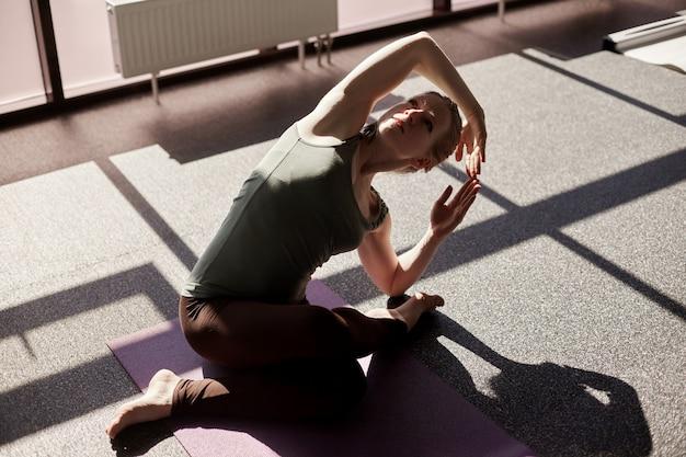 Een aantrekkelijk meisje zit in kleermakerszit, bukken, het uitvoeren van een yoga asana. het meisje houdt zich bezig met yoga in een moderne studio