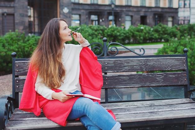 Een aantrekkelijk meisje zit op een bankje.