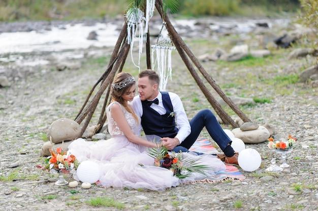 Een aantrekkelijk pasgetrouwd stel, een gelukkig en vreugdevol moment. man en vrouw knuffel en kus in vakantie kleding. bruiloft cermonia met boho-stijl dãƒâ © cor aan de rivier in de frisse lucht.