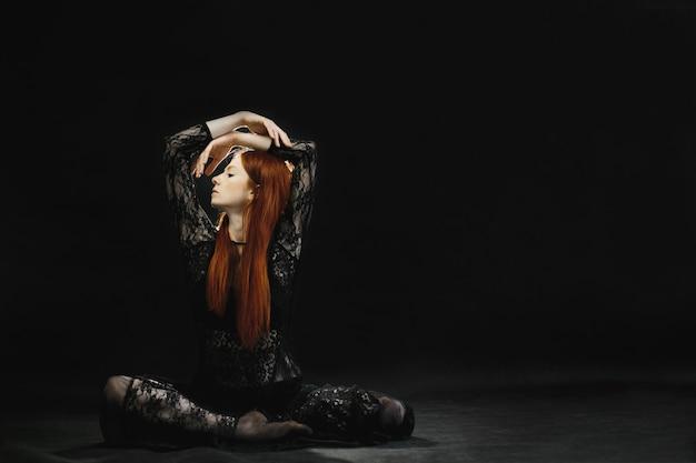 Een aantrekkelijk roodharig meisje in zwarte lingerie vormt in de studio